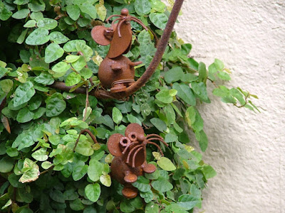 these rusty little mice are part of a garden gate