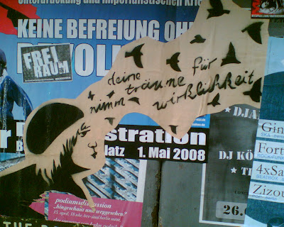 "graffit of a person's half-smiling face, next to the words """"graffiti of a person's half-smiling face, next to the words ""nimm deine träume für wirklichkeit"", all of which is surrounded by small birds"