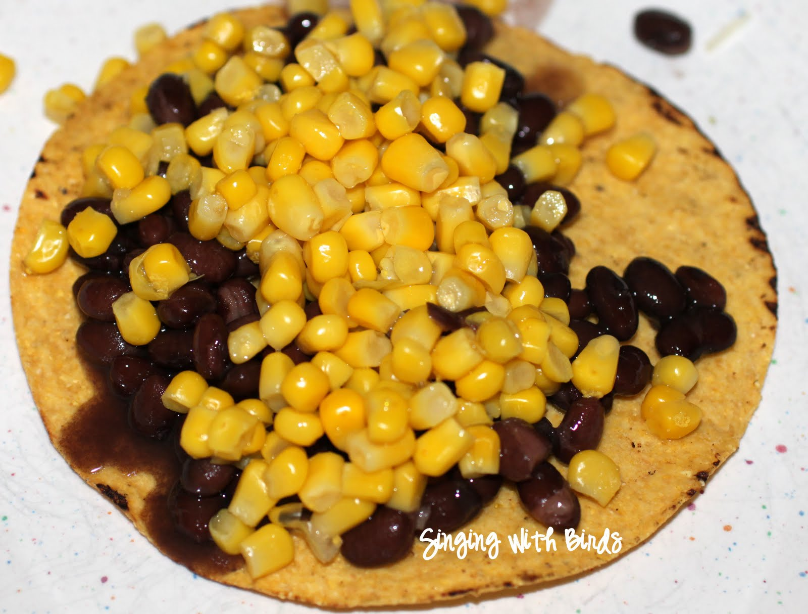 ... on each plate. Add drained black beans, corn and shredded cheese