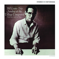 Bill Evans with glasses with his hands on a white table looking at the camera. Album cover.