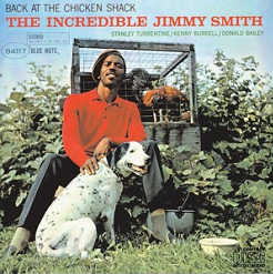 Jimmy Smith is seated in front of a chicken shack holding a dog by the lead in front of him. Album cover.
