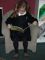 NAMC montessori education builds development reading girl in chair