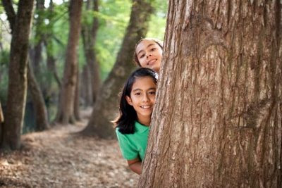NAMC montessori philosophy nature nurture whole child girls behind tree