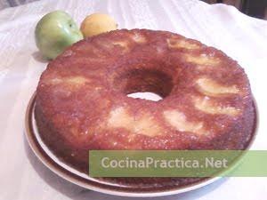 Cocinando, torta invertida de manzanas presentada en la mesa junto con una manzana verde y un limón
