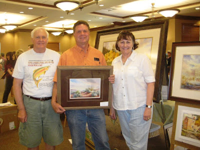 Larry and Rebecca Isakson with artist Roland Lee and the painting they purchase by silent auction