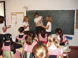 Fotografía de sala de clases, frente a la pizarra, una profesora y dos estudiantes desarrollan una actividad con una pelota