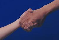Fotografía de dos manos estrechadas, una de adulto y una de niño, sobre un fondo azul