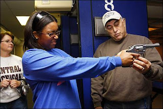 Cicely Howze of Livonia practices her hand position and the pressure needed to pull the revolver's trigger as instructor Cpl. Jim Combs of the Wayne County Sheriff's Office talks her through it during a women-only permit class at a shooting range in Westland. (Bryan Mitchell / Special to The Detroit News)