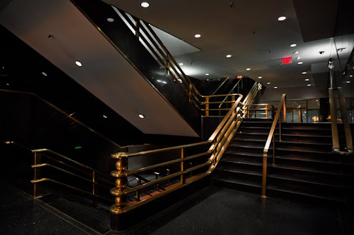brass railing art deco railings hallway staircase 30 Rockefeller Center interior brass column granite black beige NBC, 30 Rock, GE building, modern open lobby, RCA building