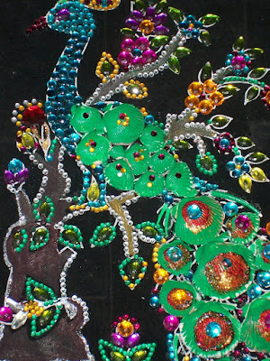 This is the portrait of a peacock made with gem stones.
