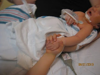 Big brother holding baby Mason's hand in NICU