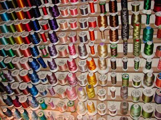Colorful embroidery threads hanging on a wallmounted thread rack