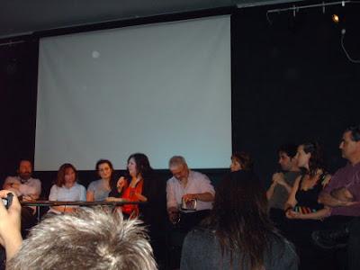 Todos los escritores de la antología, sentados de frente al público.