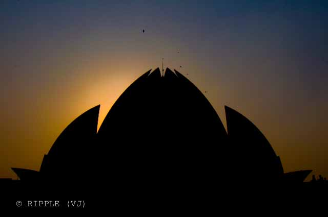 Sunset View @ Lotus Temple, Nehru Place, Delhi: The Baha'i House of Worship in Delhi which is popularly known as the Lotus Temple due to its flower like shape, is a Bahai House of Worship and also a prominent attraction in Delhi. It was completed in 1986 and serves as the Mother Temple of the Indian subcontinent. It has won numerous architectural awards and been featured in hundreds of newspaper and magazine articles.: Posted by Ripple (VJ) on PHOTO JOURNEY @ www.travellingcamera.com : ripple, Vijay Kumar Sharma, ripple4photography, Frozen Moments, photographs, Photography, ripple (VJ), VJ, Ripple (VJ) Photography, Capture Present for Future, Freeze Present for Future, ripple (VJ) Photographs , VJ Photographs, Ripple (VJ) Photography : Again a silhouette of Lotus Temple but colors on the back are not so good... This shows the dullness of poluted sky in Delhi :-(The temple is shaped in the form of a half opened Lotus Flower and the main structure encircled by nine ponds. There are nine doors that lead to the central hall. Number nine is considered sacred in Bahai faith which depicts all the major nine faiths of the World. The central hall suggests that all nine religions are dedicated to the sole God. This central hall can manage 2500 people at a time.
