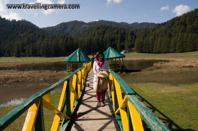 My adventurous self finally took over this March and I headed to the hills. Dalhousie beckoned me with its tantalising name and fame. During my three days two nights stay in Dalhousie, I stole a day to visit Khajjiar and Chamba. I am so glad that I did. Khajjiar is unbelievable. Who would have imagined this expansive pastureland surrounded by Deodars right in the middle of a Very Hilly Terrain. When I reached there, blissfully, there wasn't much crowd. Usually, the entire ground is full of people. In this paricular Picture, the absence of human activity helps in emphasizing the magnificient Deodars.A close up of Deodars. Look at the two men on the left to get an idea of the sizes of these giant trees.A Colorful bridge leading up to the middle of the lake.Hills reflected in the water of the lake. Me on the Bridge. My guide obliged me with by clicking this picture.A horse grazing peacefully. I don't think I have ever got so close to one except at weddings.Another Horse. This one was rather skinny though considering the amount of fresh grass it has access to.Cloud rising out of the hills reflected in the lake. There were several beautiful buildings around the ground. Many of these were restaurants.Me next to a broken bridge. A Philosophical Setting.Chamba, Colorful, Hill Stations, Hills, Himachal Pradesh, Holidays, Lakes, Nature, Sky, Snow Covered Hills, Trek, Khajjiar: Posted by Vibha Malhotra on www.travellingcamera.com:Mesmerising Khajjiar