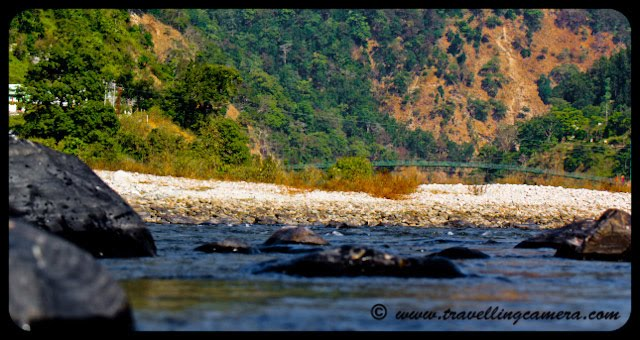 Ramganga River near National Jim Corbett Park: Posed by VJ @ www.travellingcamera.com: Two years back we choose Jim Corbett for year end trip and stayed at Ram Ganga Resort at the banks of Ramganga River. Here are few photographs of Ramganga River in Uttrakhand.Ramganga West river originates from Doodhatoli ranges in the district of Pauri Garhwal, Uttarakhand state of India. The river Ramganga flows to south west from Kumaun Himalaya. It is a tributary of the river Ganga, originates from the high altitude zone of 800m-900m. Ramganga flows by the Corbett National Park near Ramnagar of Nainital district from where it descends upon the plains. Bareilly city of Uttar Pradesh is situated on its banks. There is a dam across this river at Kalagarh for irrigation and hydroelectric generation.boulders strewn across the rive bed. These can be seen in almost any river as it reaches the plains.Ink blue... The river is mostly shallow with deep areas here and there. It can be treacherous.Some of these mountain rivers have slogged over thousands of centuries to carve their ways through the mountains. Erosion is an example of slow and steady wins the race...All around the ram ganga resort, the landscape is hilly with some excellent trekking trails. This photo was shot from one of them.Ram Ganga Resort at the banks of the Ram Ganga River.
