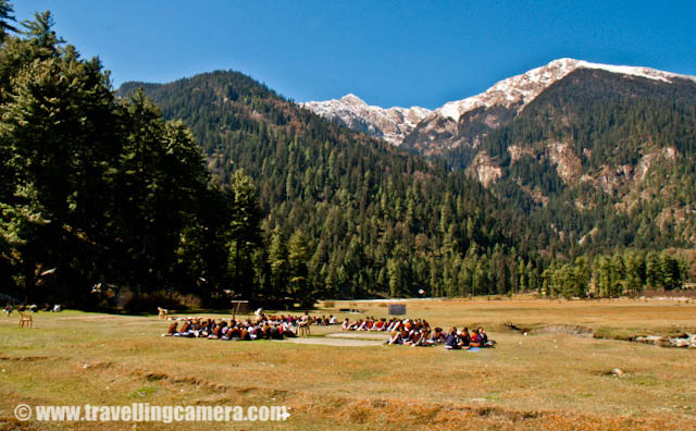 One complete day well spent at Kullu Sarahan - 4th day of MTB Himachal 2010-01.jpg: Posted by VJ SHARMA on www.travellingcamera.com : During MTB Himachal 2010, there was only one rest day for riders and they had chosen most amazing place for having rest... although no one wanted to rest inside the camp.. Most of the riders thought of exploring the natural beauty of the places around Sarahan Villlage... Here are some of the photographs showing the whole fun we had during the fourth day of MTB Himachal....A view of Sarahan Village in the middle of snow covered mountains... The village has a huge ground near Government school...Three shining trees on the other end of the village... There are few shops around these trees and people have some guest houses for visitor.. Its a beautiful village, but there is no decent hotel or guest house... But there is a HPPWD guest house on the top of a hills on the side of the ground you see in first photograph...Some houses around the main ground in Sarahan village...There were some water streams flowing around this ground and they had chilled water.... melted snow from the surrounding peaks...School Children enjoying their studies in the open... Imagine how much exciting it would be to have a class in a huge green ground surrounded by snow covered peaks... and water streams flowing on both sides of your class area....There was a small dairy in the village and the milk is delivered to the nearest town and it was most difficult task to deliver it on time everyday... No transport and one has to go 12 kilometers down to reach the place and come back....Another photograph of Open School in Sarahan Village of Kullu Distrcit in Himachal Pradesh... Masti ki pathshala...Its evening now and time is to go back to our camps for bonfire, snacks and booze....A typical roof of a Himachali House... This roof is made up of slates created from a very hard/shining stone... First a wooden framework is created and these slates are installed on top of that... Its very important to have slanting roof in these areas...And of-course, this break gave us an opportunity to make new friends... Inside the camp and outside of it...One another shot I wanted to share here :)