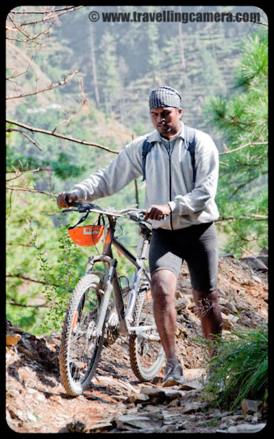 Mountain Hiking and Biking Stretch on Second Day of MTB Himachal 2010 : Posted by VJ SHARMA on www.travellingcamera.com : Hope you have already checked photographs of first two days including River Crsossing... Here are few photographs of mountain climbing after River Crossing.. During this stretch, every rider had to climb few mountains with there bikes and there was no scope of riding them.. So, sometimes they had to keep those on their shoulders and try to drag if possible :) .... check out what all happened during this...It was really hard to trek even without any weight with you and I was wondering how those guys were dragging these cycles on those steep hills.... Sometimes, there was no scope of dragging, and they had to take them on their shoulders...Here is a Photograph of six riders climbing up the mountain with their bikes... Great Spirit !!! I think first climb was of 1.5 kilometers and it was the most difficult ... Solomon finding out creative way of playing on hills... All these things kept him busy and had no time to think about tiring trek :) ... I never saw any signs of tiredness on his face... Always happy and cheerful..In last photographs he was rolling his cycle on arrow and rough paths of the hills and here he has taken it on his head... Another style... I think he had tried ll possible activities with his bike on this hiking session...Jimsee was very happy to see all the natural beauty of the place and she was one of the top appreciators in the group :)  Hills, Flowers, Insects, Butterflies, Snow, colors, apple orchards etc...Finally everyone reached a small village on hill top after 1.5 kilometers trek...  Here is another enthusiast from Dehradun in Uttrakhand ; Mr. Ranjan Nautiyal... I had few chances to chat with him and liked his company during this time... He was very happy about the event and had a very different/interesting thoughts about the event... will share sometime :) After reaching the peak, we had to move towards the other village