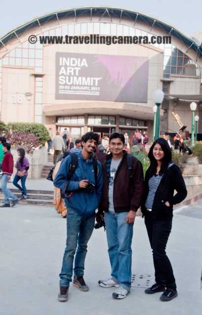 A Day well Spent at India Art Summit 2011 @ Pragati Maidaan, New Delhi, INDIA - 22nd Jan 2011 : Posted by VJ SHARMA on www.travellingcamera.com : Recently India Art Summit 2011 was happening in Pragati Maidaan of Delhi and some of my friends planned to have a visit on weekend to explore what all happens in this summit.. Finally we went there on saturday(22nd Jan 2011) and reached at Pragati Maidaan Metro at 11:40 am... After reaching at the entry gate, we saw a huge line and the end was not even visible to us.. The line was for entry and there was another smaller version for getting tickets... Finally I also reached the counter and asked for three tickets and the person managing that counter asked for 600 rs... I realized that I am short of money and asked one of friend to give 300 rs.. After getting tickets, we also followed the queue and entered into the hall where ART SUMMIT was going... Here are few photographs I could click inside the summit area... Check out !!!Here is a metal art showcased by one of the French artist !!! Are you able to see the art? Its the one is main focus, please see the bottom part of this photograph ;) A gold plated spherical structure surrounded by multi-layered shapes which are made up of brass.... There were some other interesting art works showcased here... I have lot of photographs of these metal artworks and will try to share more in future.... There were lot of artists and visitors from various parts of the world... Here is a lady waiting for other friends to come and go inside to see the fabulous work by different artists !!! I clicked this photograph very quickly with some zoom and wanted to have another photograph of her baby but couldn't :(  She caught me... She was standing inside the Art Summit hall and was talking to someone... I wanted to have her side face with some of the paintings hanging on the right wall... Suddenly she turned and I was not able to compose a good shot... Still I acted like I am shooting something else and after having 2-3 shots moved ahead...India Art Summit is very famous among the high class society of Delhi and many celebrities come here to see the wonderful work & buy something for them.... There were lot of metal arts in INDIA ART SUMMIT and man of them were from other parts of the world...  When we just entered into the main hall & started looking at the arts, we were not very impressed and one of friend even thought of becoming an artist because he thought it's easier that Software Development :) As we spent more time and talked to various people around, we got to know that how much hard work and thoughts go in creating a single art... Here is an artwork with a face having lots of other elements and a hidden face... A lady standing there was explaining about this art and there were lot many folks listening... We were not able to make out much out of that talk and thought of moving ahead... but this one was one of the popular artwork in the summit (A general guess by looking at the crowd, because in Delhi wherever you see crowd is known as a popular place, especially any eating place...)I liked these hanging lamps... I went to my childhood when I saw these first time at my Grand Parent's place and after that I couldn't find them anywhere... There was a huge Art project based on lighting and these lamps hanging around..Another Metal Art !!!Don't know much about this particular artwork but looked like something made up of stone... but not sure, so no comments !! But I liked it !!! It was placed in the middle of a painting gallery..This was an amazing work and this was the place where everyone was spending more time as compared to other stalls... We saw lot of mirror arts in ART SUMMIT and all of them were amazing... This was a mirror created of various triangular pieces... As you go closed to the mirror, the partition size seemed to decrease and moving backward it was increasing... By the reflection inside the mirror is mine with Camera...Again the same art with few more elements in the photograph for better composition !!!Here is gang... I asked them to stand there to have a photograph as a proof that they visited ART SUMMIT... I was expecting them to click one of mine photograph as well but none of them offered :)Mr Ankit Sood on the left - A student of Delhi College of ART, Deepak Gupta - who is going have long hairs soon and planning to exhibit his artwork soon... Anchita Dogra will support Deepak in the beginning and will move on with her own choice of art soon !!! After a good day at INDIA ART SUMMIT we went to Shri Ram Center to have lunch because it was very costly inside Pragati Maidaan :) btw Ankit took us there to have some silli potatoes and no one liked them :)