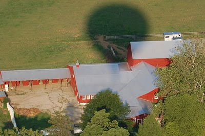 Balloon shadow crossing farm buildings.