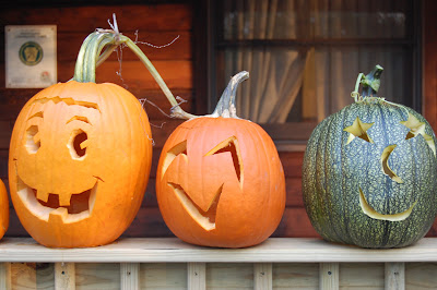 Jack-o-lanterns on a porch railing.