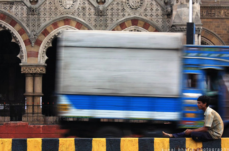 mumbai street photography man sitting on divider vehicles passing by kunal bhatia