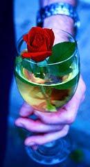 mano masculina sosteniendo una copa con agua y una rosa dentro de ella