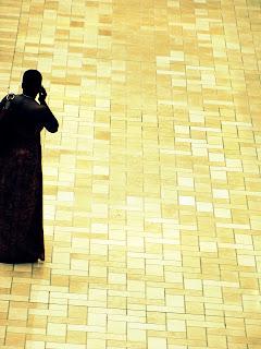 Silueta de persona africana hablando por celular, sobre piso de cerámica.