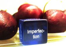 Verfaulendes Obst und ein Würfel mit Aufschrift 'Imperfection'
