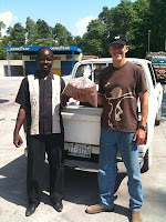 Mark Kirwin and a man from Port-au-Prince holding disaster relief supplies.