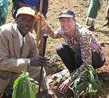 The photo is of Angela Kirwin, KIRF Co-Founder, at a soil remediation project in Arusha, Tanzania. Local farmers are trying to re-claim farm land ruined by soil erosion by planting indigenous trees and food plant varieties.