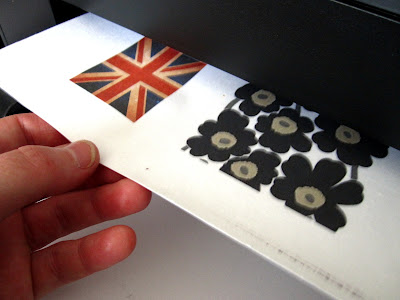Hand pulling a piece of printed fabric from a printer.