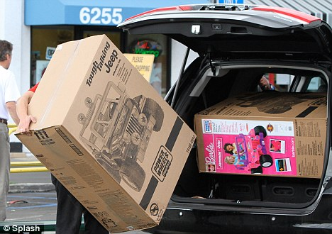 Tight fit: A Toys R Us sales adviser tries to fit the two baby jeeps into