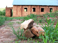 Stones mark the spot of a new borehole for drinking water in Cheelo with the church in the background