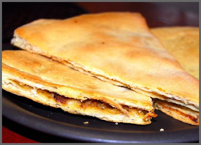 A covered North African pizza stuffed with onions and spices