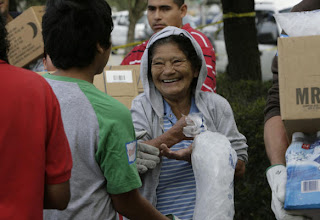 Blanca Linares, 76, originally from El Salvador, smiles as she gets a bag of ice from 13-year-old volunteer Daniel Medrano in Galveston