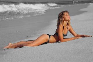 Garota deitada na praia, agora em preto e branco destacando corpo em cores