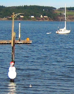 Image of sailboat at anchor and snowman on a piling.
