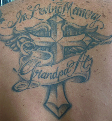 A heart with wings and cross tattoo at man's back.