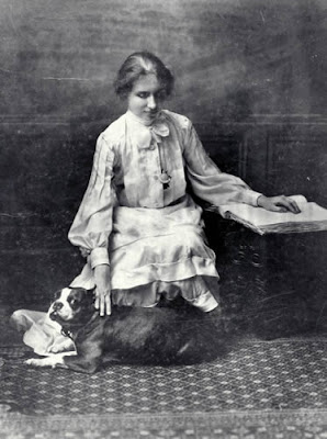 A picture of Helen Keller reading Braille with her left hand and petting her dog with the other hand