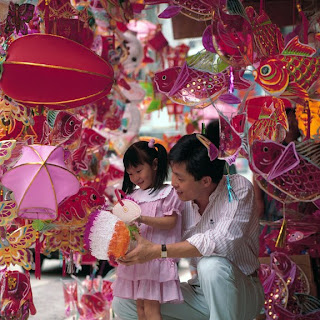 Dad and his daughter are preparing for Mid autumn festival