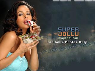 Malaika sherawat the most glamorous girl in bollywood india.  In a light green shirt earing fruits