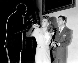 From right to left: Alan Curtis, Evelyn Ankers and the outline of Jon Hall in a publicity still for The Invisible Man's Revenge.