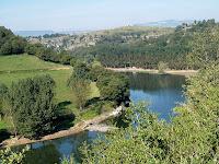 En primer terme els Camps de Trabosc i al fons enlairat el diòsit d'aigües