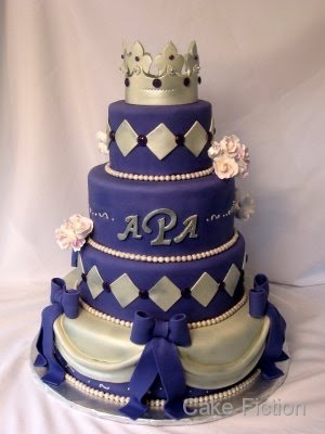 Purple fondant with silver accents covers the cake with more fondant drapes