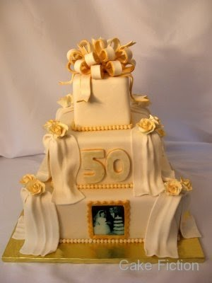 A square three tier ivory cake with gold accents for a 50th Wedding