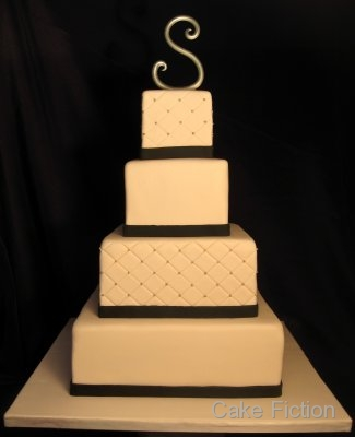 A four tier quilted diamond ivory wedding cake with black fondant ribbons