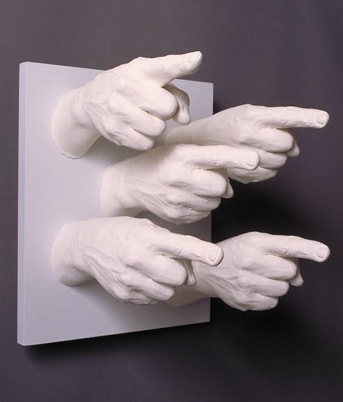 A sculpture on a wall made up of white hands pointing fingers angrily outwards