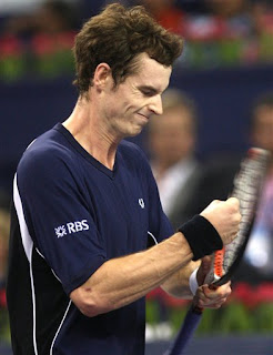 Andy Murray hits his racket in frustration