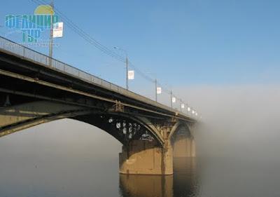 Арочный мост через реку в тумане.